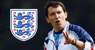 "England manager Graham Taylor is seen open mouthed and pointing towards the camera with two fingers alongside an England football ""Three Lions"" crest."