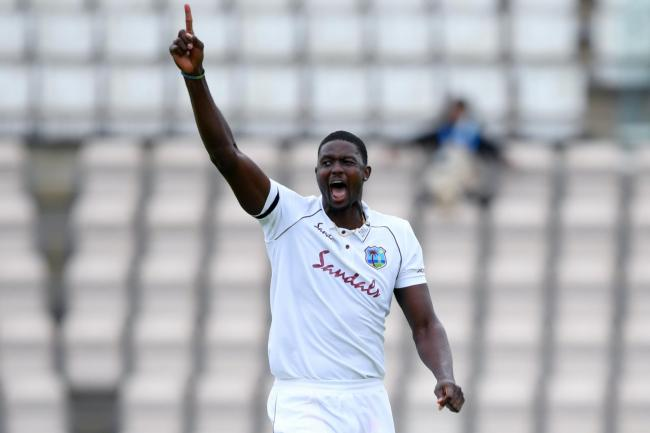 West Indies captain Jason Holder holds his arms aloft during the first test match against England